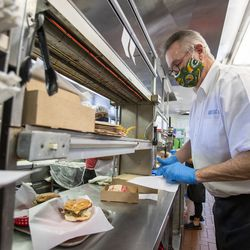 Longtime Hires Big H employee Jim Merrill assembles an order as he works his last week of shifts at the burger joint in Salt Lake City on Friday, Jan. 8, 2021. Merrill has worked at the company for 52 years.