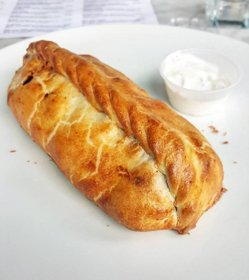 A big, doughly lamb vindaloo pasty from Cornish Pasty Co sits on a white plate.