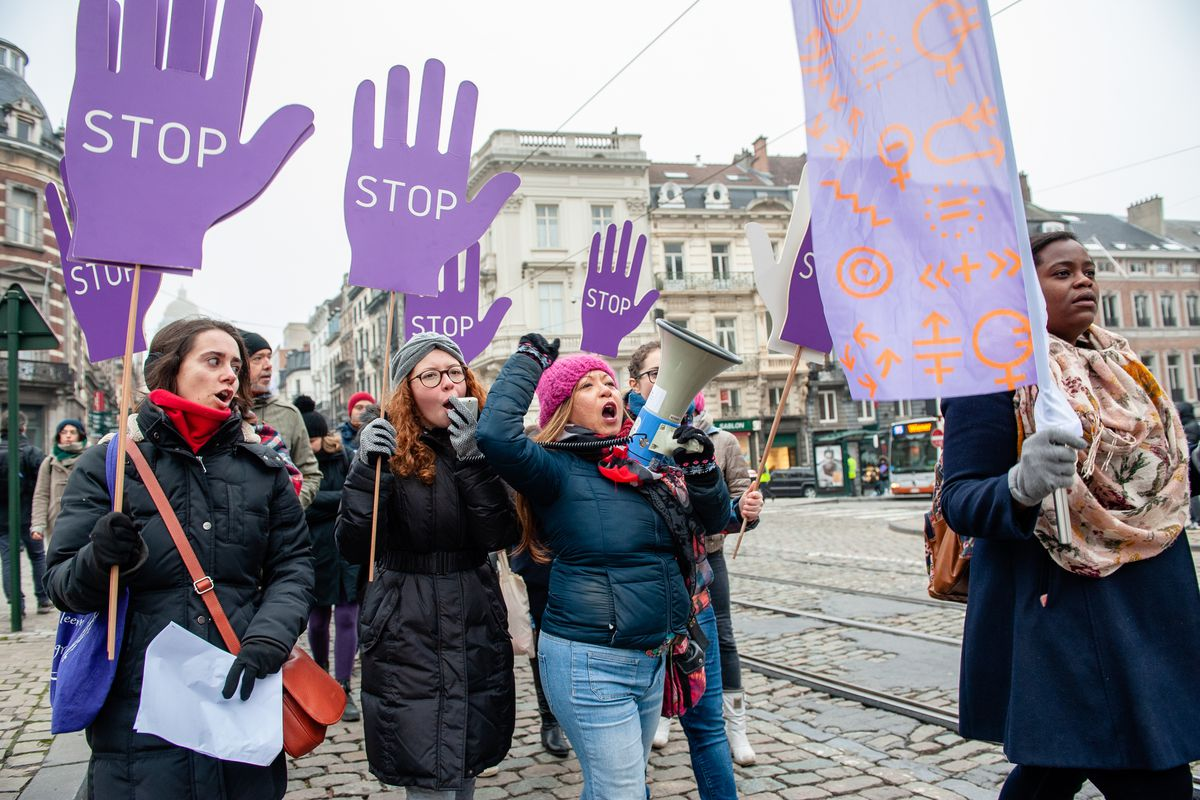 """Demonstrators on a street in Belgium carry large purple signs, shaped like hands and printed with the word """"stop,"""" as another demonstrator carries a colorful flag adorned with gender symbols."""