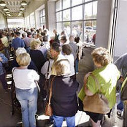 Hundreds of people, mostly senior citizens, wait in line on Tuesday to receive flu shots at a Costco store in Winchester, Va.