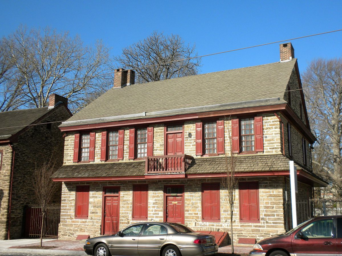 The exterior of Grumblethorpe in Philadelphia. The facade is brown brick and there are red shutters.
