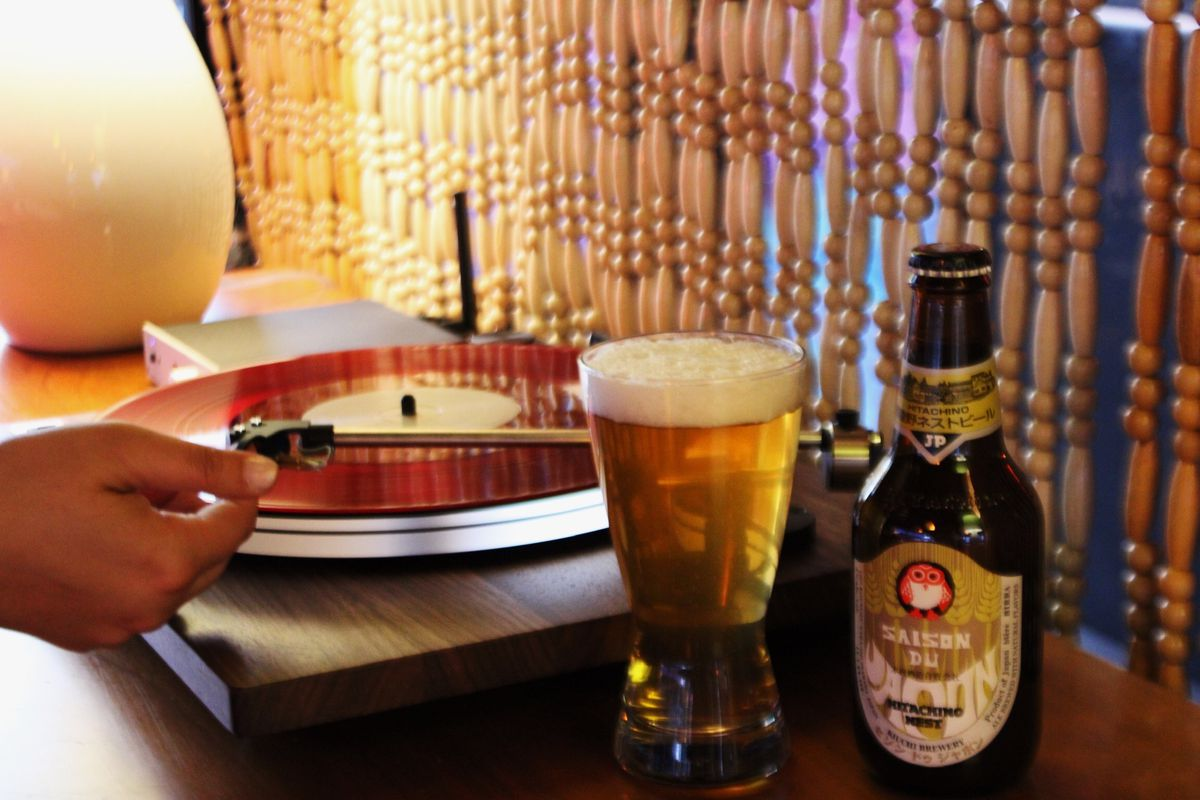 A hand operates a record player. There's a beaded curtain in the background and a glass and bottle of Japanese beer in the front.