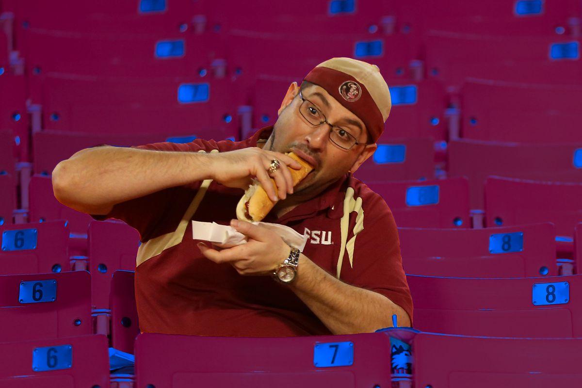 A man eats a hot dog.
