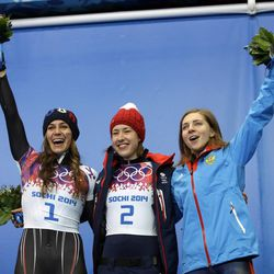 From left to right, silver medalist Noelle Pikus-Pace of the United States, gold medalist, Elizabeth Yarnold of Great Britain and bronze medalist Elena Nikitina of Russia pose during the flower ceremony after the women's skeleton competition at the 2014 Winter Olympics, Friday, Feb. 14, 2014, in Krasnaya Polyana, Russia. (AP Photo/Dita Alangkara)