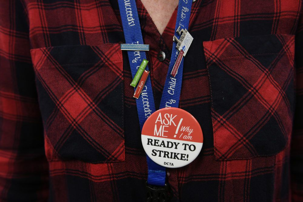 Sharyn Kline, a 2nd grade teacher at Park Hill Elementary school wears pins on her lanyard as she sits in a packed room to listen to continued negotiations between DPS teachers and administrators.