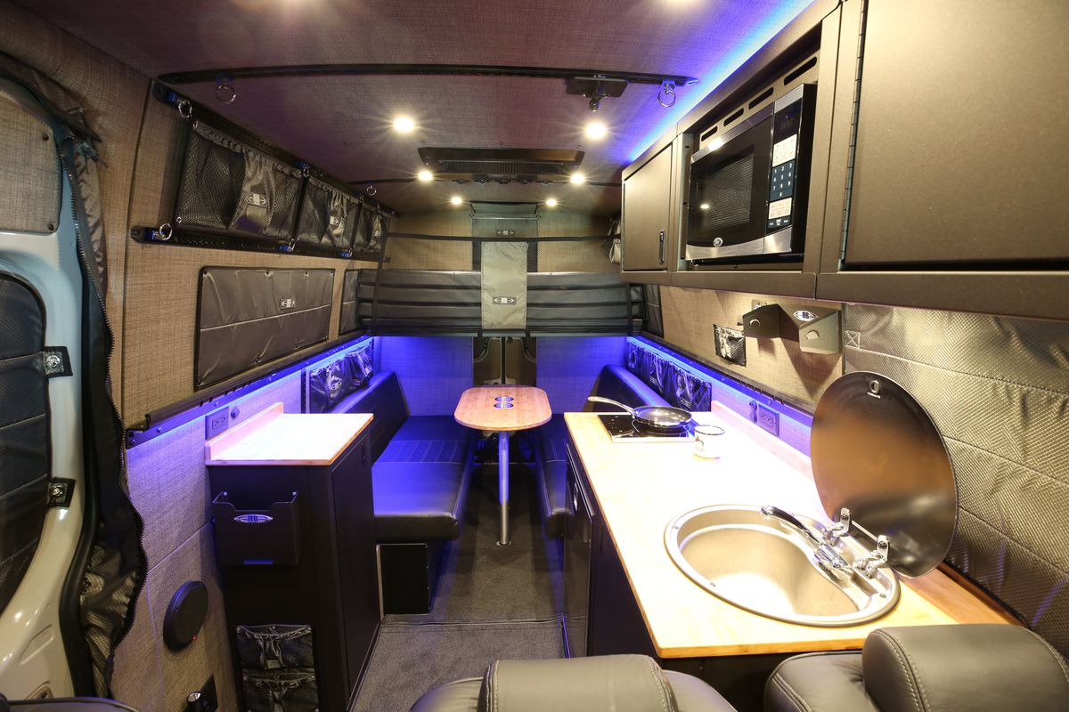 The interior of a camper van. There are seats, a table, and a kitchenette with a sink. There is a microwave and various storage compartments.