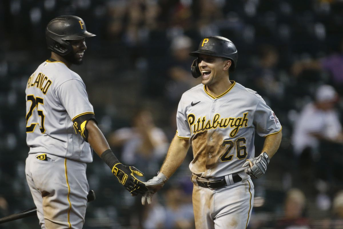 Adam Frazier of the Pittsburgh Pirates celebrates with Gregory Polanco of the Pirates after scoring against the Arizona Diamondbacks following a bases loaded walk to teammate John Nogowski during the seventh inning of the MLB game at Chase Field on July 21, 2021 in Phoenix, Arizona.