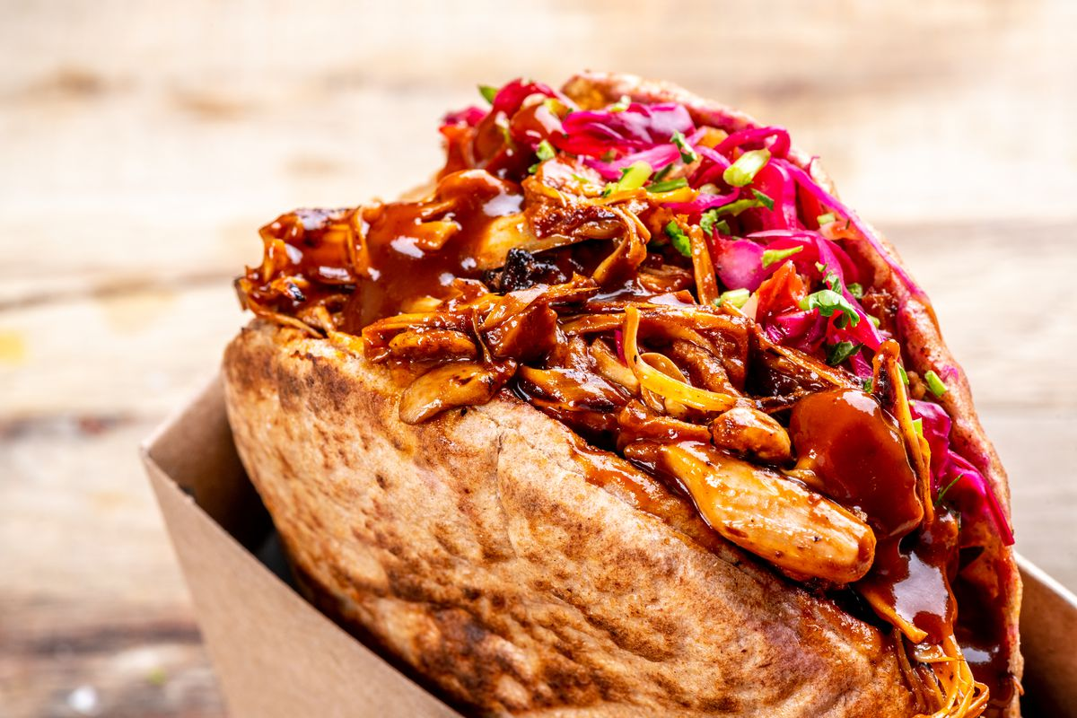 A close-up of Shouk's BBQ Jack pita brimming with saucy griddled jackfruit and cabbage salad