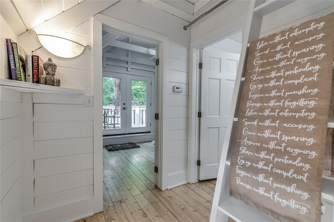 A white landing area with wood floors.
