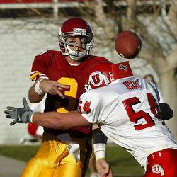 USC quarterback Carson Palmer lets go a ball as Sheldon Deckart hits him as  Utah beat USC 10-7 in the Las Vegas Bowl on Dec. 25, 2001. Photo by Tom Smart