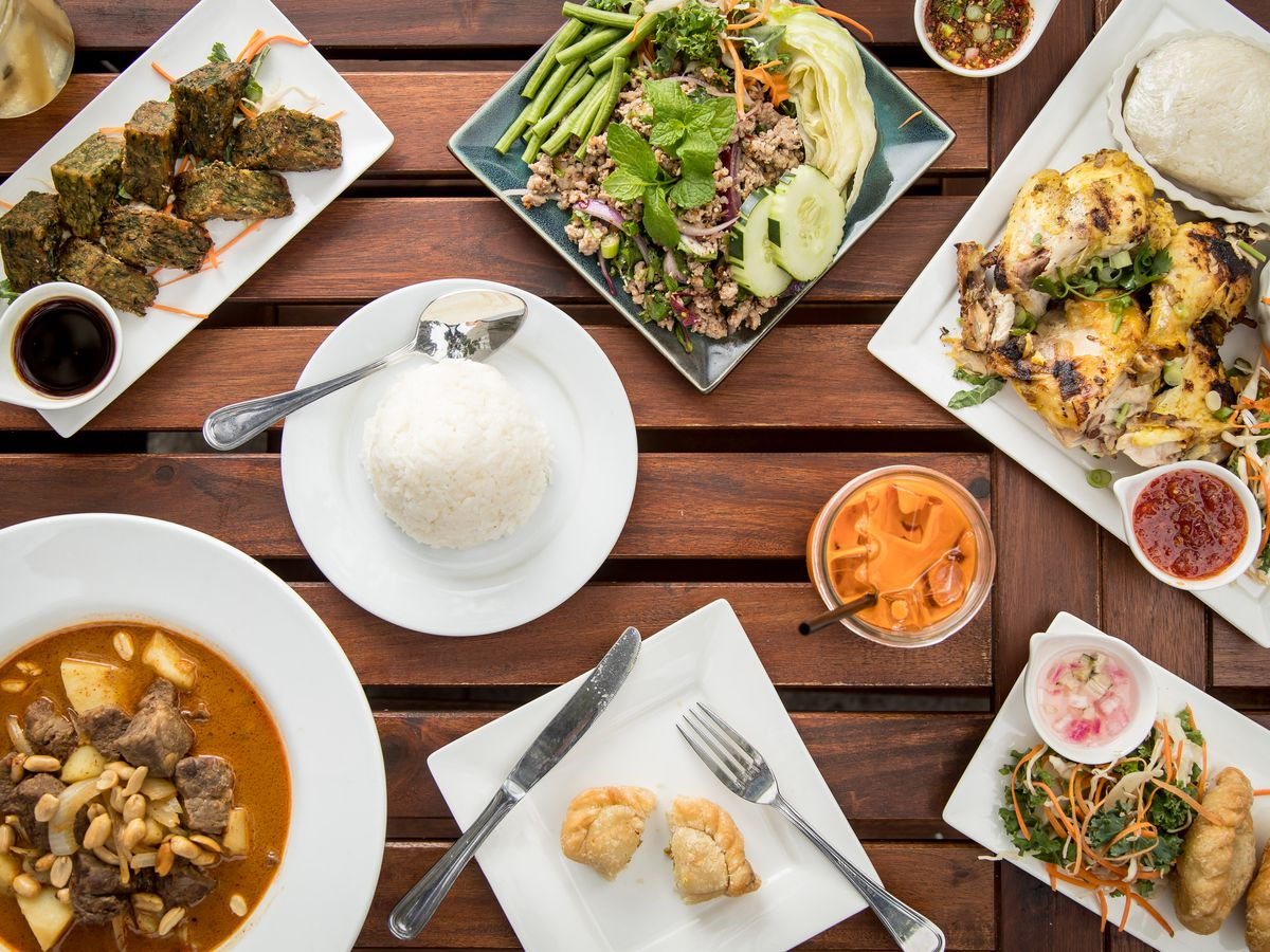 A spread of Thai food on a wooden table.