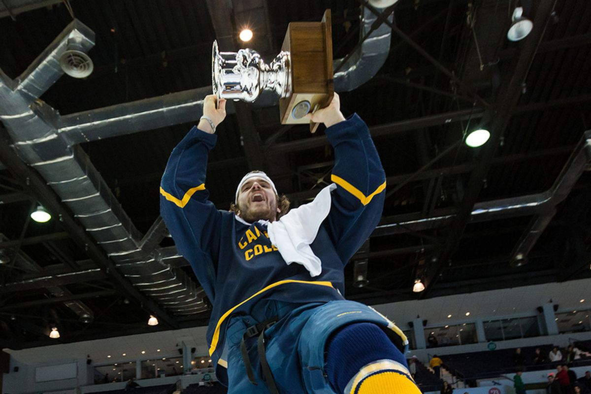 Canisius College's Kyle Gibbons celebrates with the 2013 Atlantic Hockey Association Tournament trophy.
