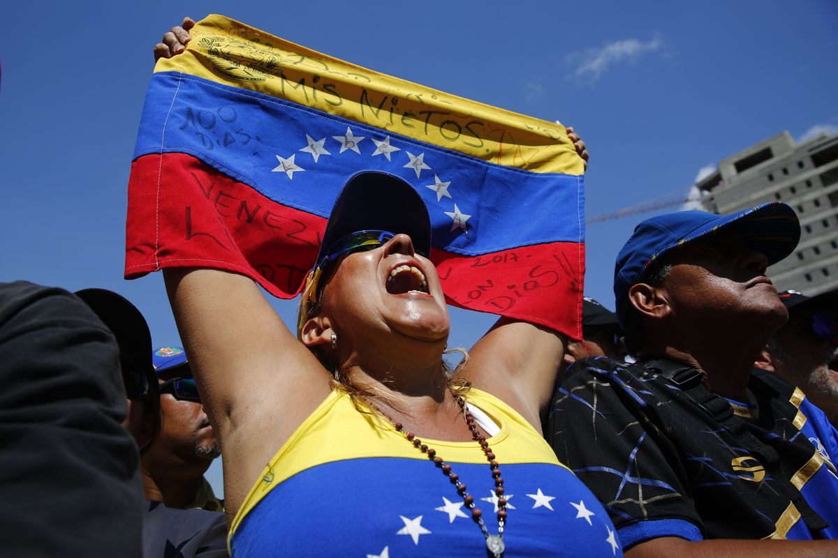 A woman shouts as opposition leader and self-proclaimed interim president of Venezuela Juan Guaidó delivers a speech during a rally against the government of Nicolás Maduro in the streets of Caracas, Venezuela on February 2, 2019.