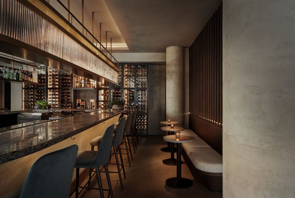 A bar with stools across from a narrow grey banquette