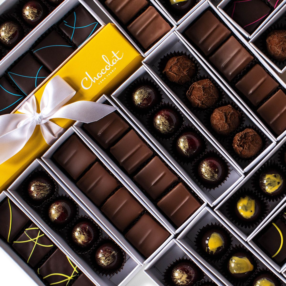 Rows of specialty chocolates in boxes.