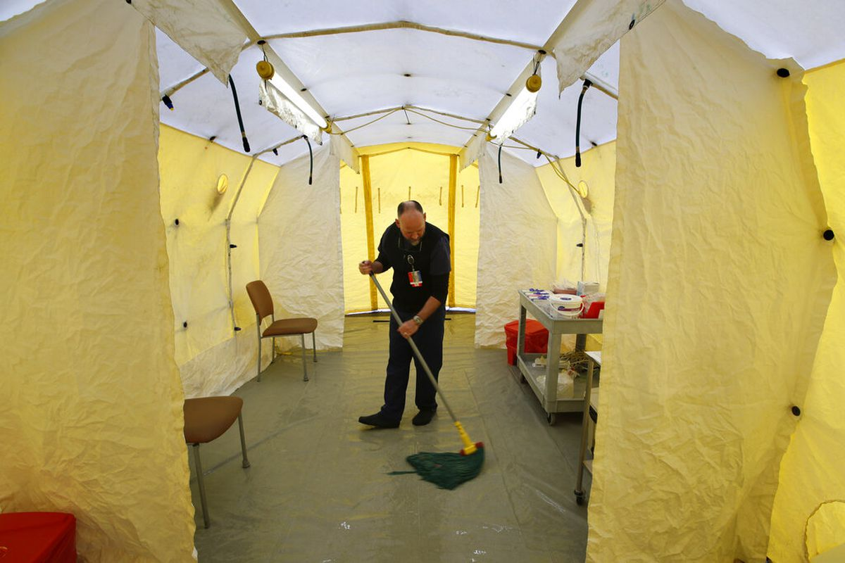 Steve Moody, director of nursing at Central Maine Medical Center, mops the floor of a tent outside the emergency entrance to the hospital