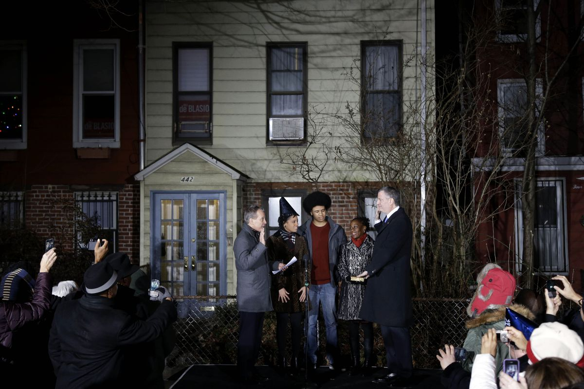 Mayor Bill de Blasio and his family stand outside of their white clapboard and red brick Park Slope, Brooklyn  home.