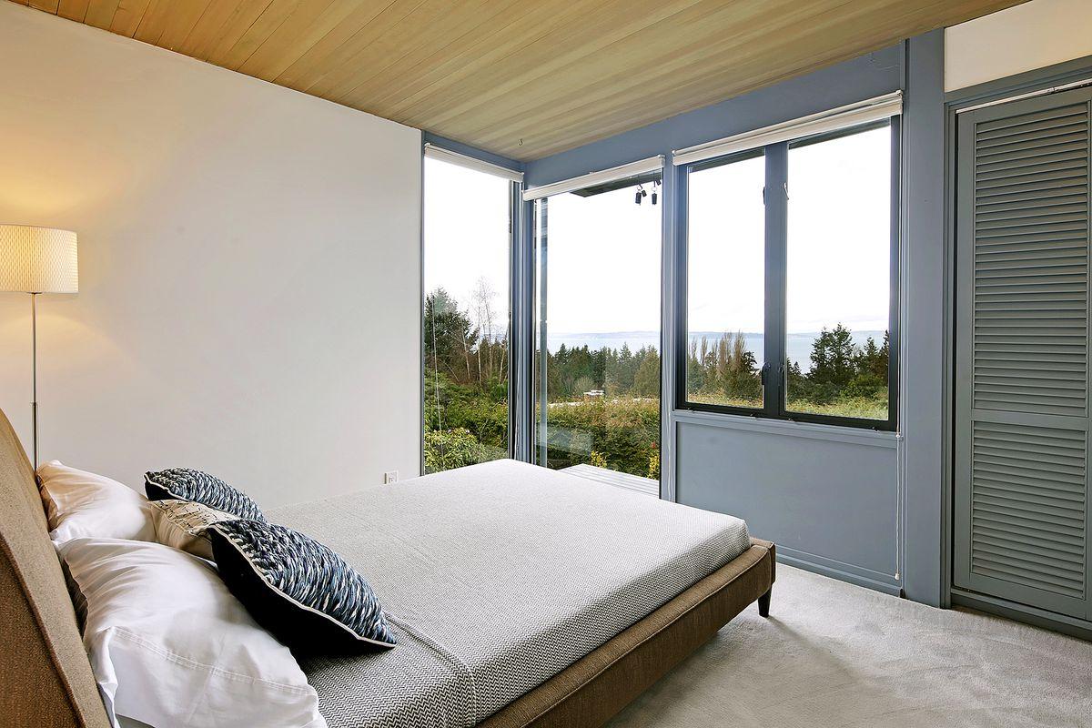 A bedroom with floor to ceiling corner windows