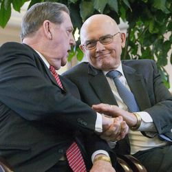 Elder Jeffrey R. Holland and Elder Dallin H. Oaks shake hands  inside the Conference Center in Salt Lake City after a news conference Tuesday, Jan. 27, 2015, as LDS leaders reemphasize support for LGBT nondiscrimination laws that protect religious freedoms.