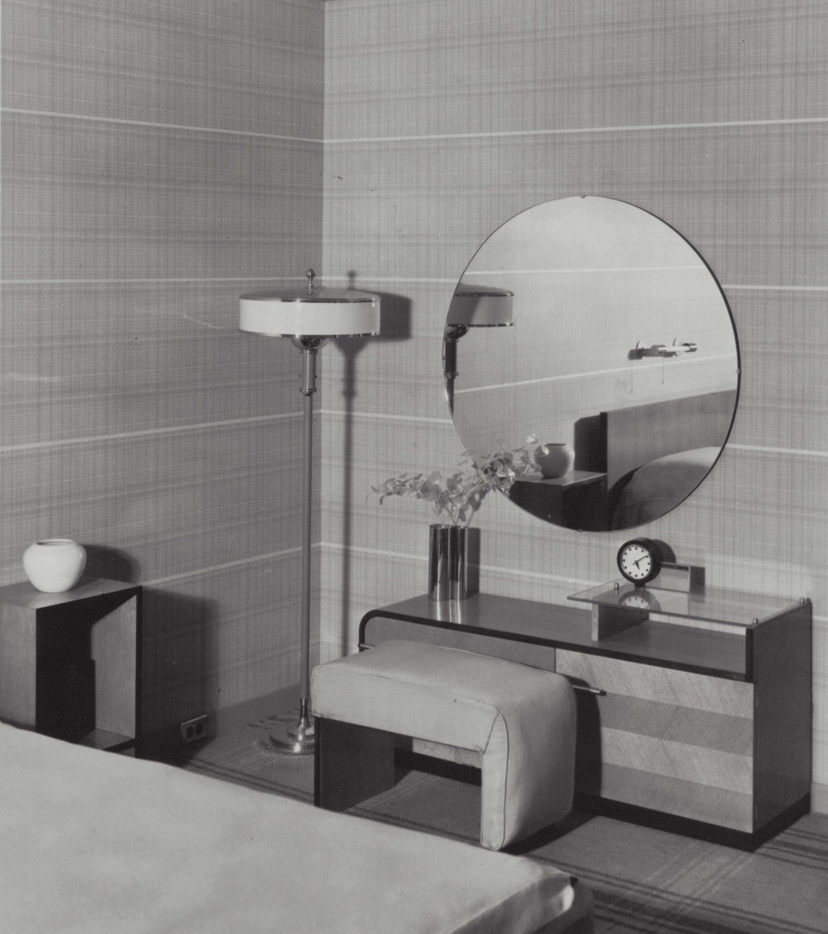 A bedroom with a chest, lamp, and mirror in Herman Miller's Design for Living House.