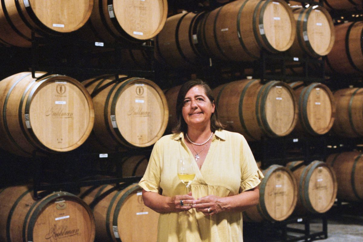 A woman in a pale yellow flowy shirt holding a glass of white wine in front of rows of wooden barrels.