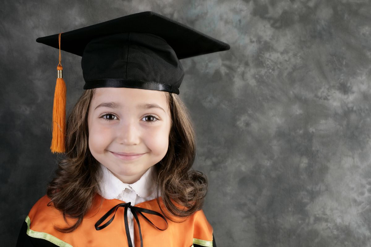 An elementary school child wearing a mortarboard and smiling for her portrait.