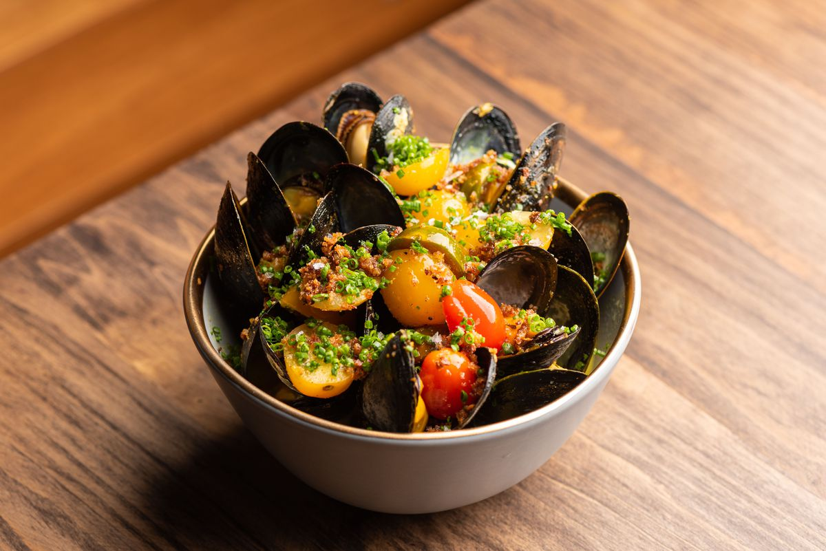 Black shelled spring mussels in a bowl with olives.