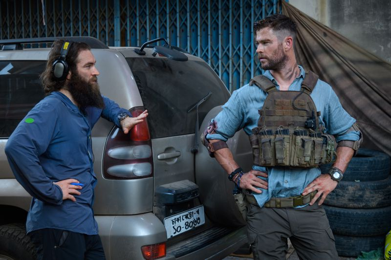 Sam Hargrave, who has a giant beard, leans on a car to talk to his bud Chris Hemsworth, who has his hands on his hips