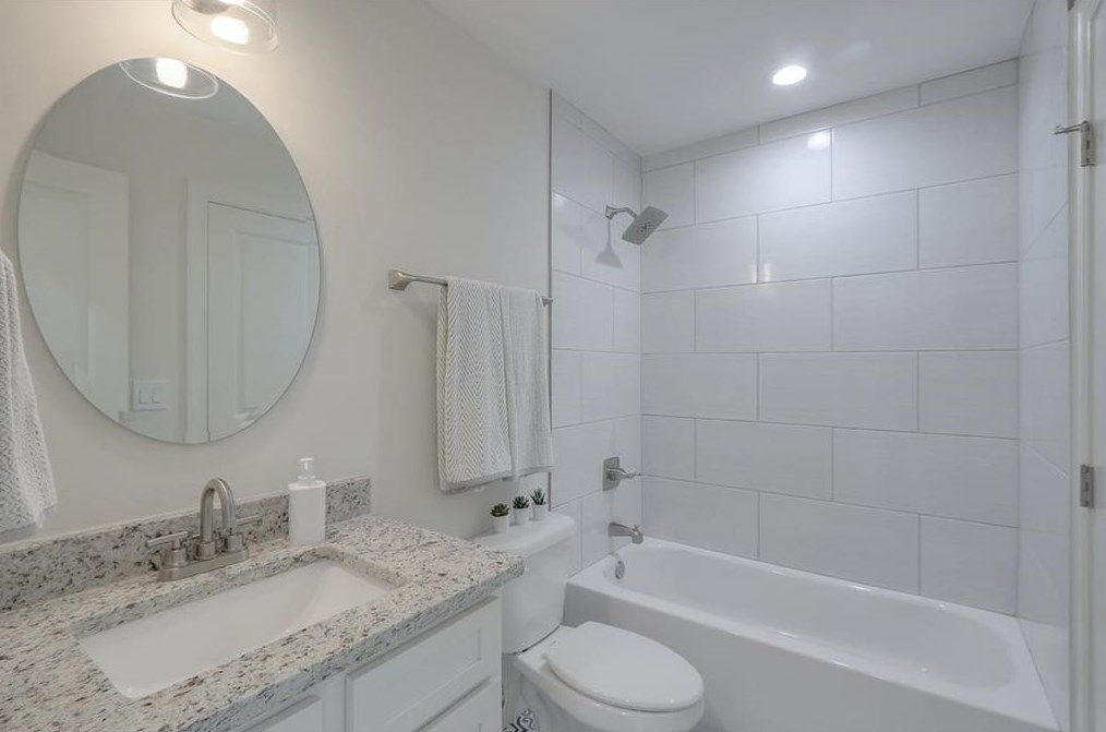 A bathroom in all white with a mirror and sink at left.
