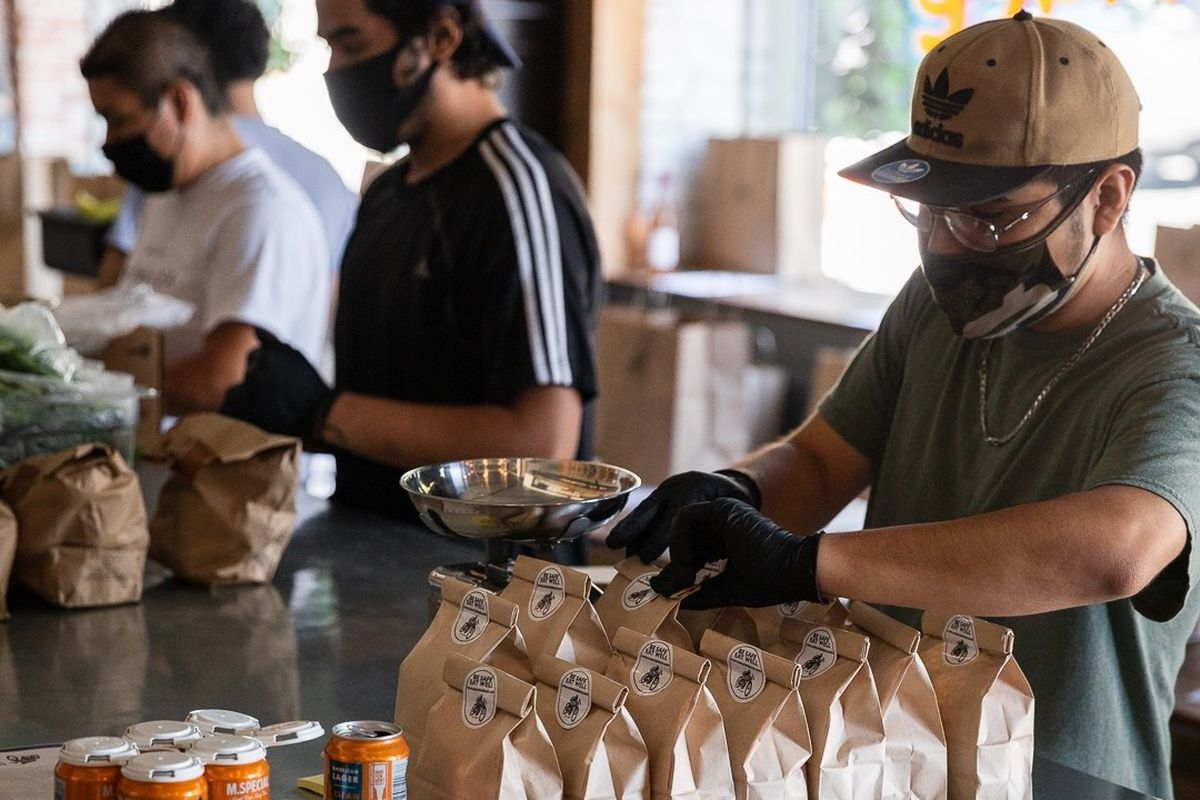 A worker in a mask bags grocery items while inside of an otherwise closed sunny restaurant.