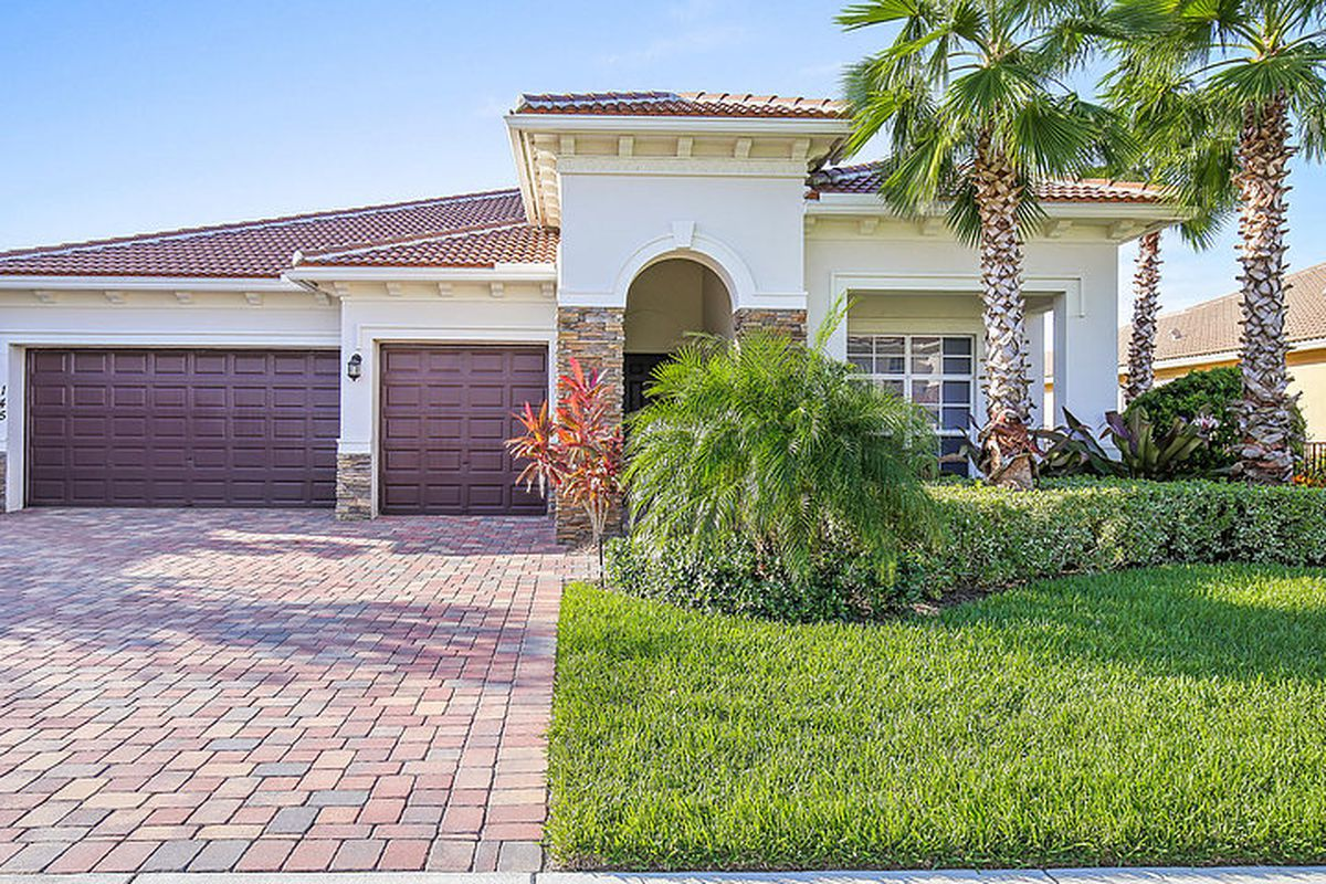 Front yard view of a mediterranean home in jupiter with a two-car garage
