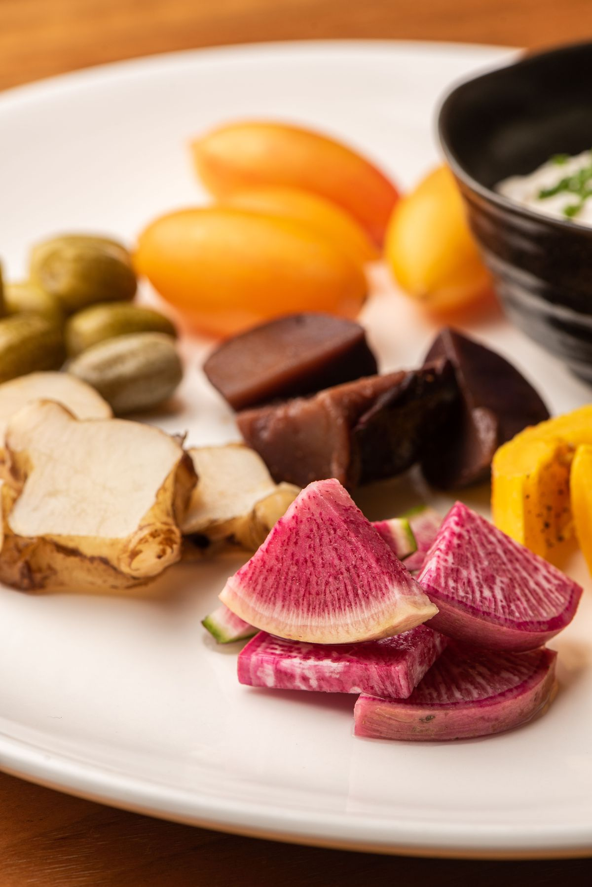 A vertical photo of pickled vegetables on a plate.