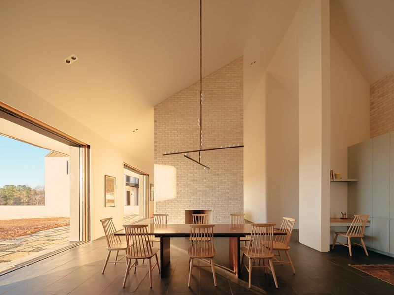 Dining room featuring tall white brick fireplace.