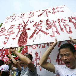 """Protesters shout anti-Japan slogans while holding a banner reading """"We won't give Diaoyu Island, but if you want the bomb, we want to give it to you"""" near the Japanese Consulate General Tuesday, Sept. 18, 2012, in Shanghai, China. The 81st anniversary of a Japanese invasion brought a fresh wave of anti-Japan demonstrations in China on Tuesday, with thousands of protesters venting anger over the colonial past and a current dispute involving contested islands in the East China Sea."""