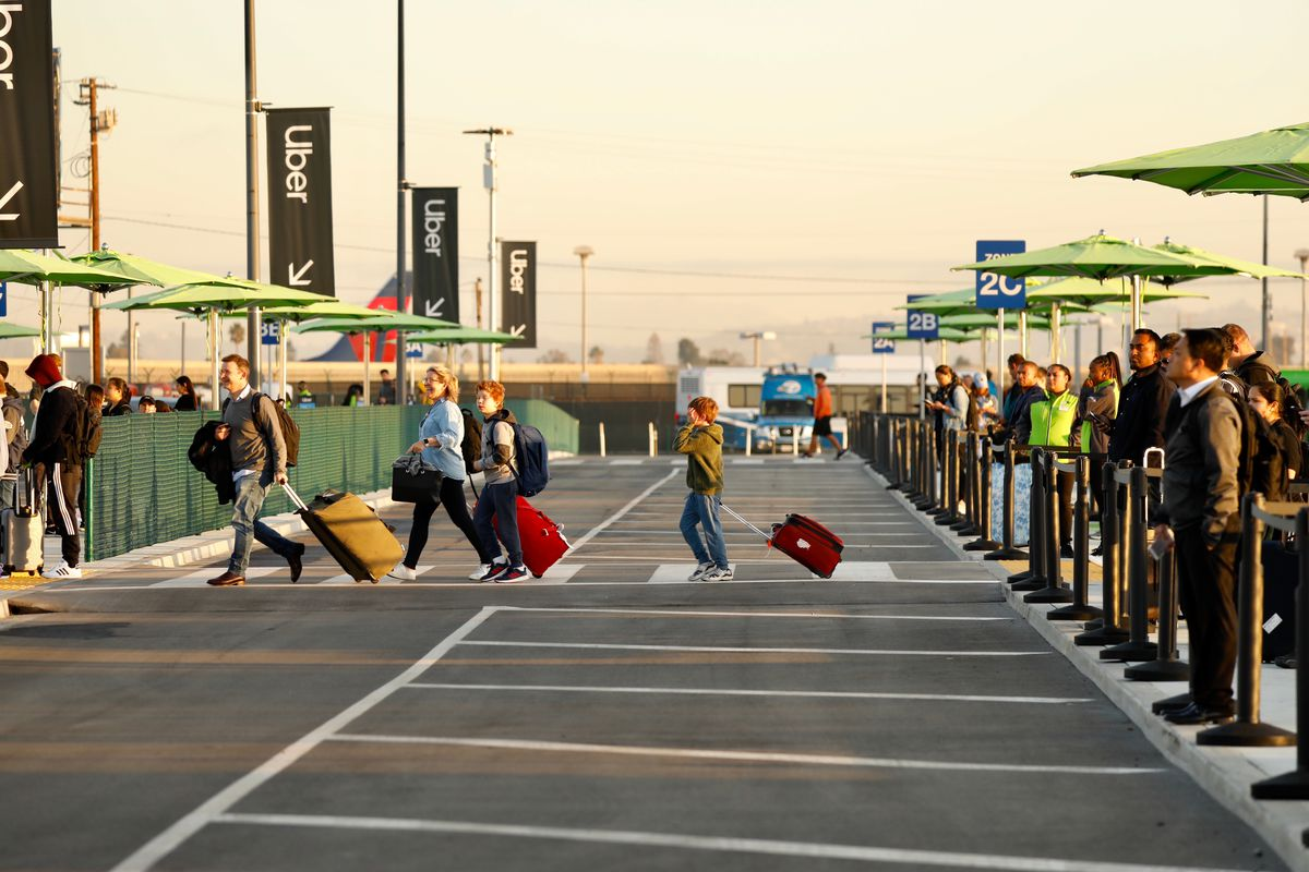 Passengers at LAX use the new passenger pickup area for Uber, Lyft and taxis