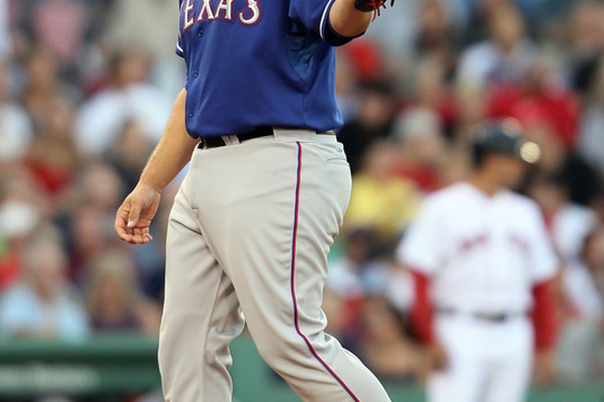 BOSTON - JULY 15:  Tommy Hunter #35 of the Texas Rangers gives a nod to Chris Davis after Davis made the out against the Boston Red Sox on July 15 2010 at Fenway Park in Boston Massachusetts.  (Photo by Elsa/Getty Images)