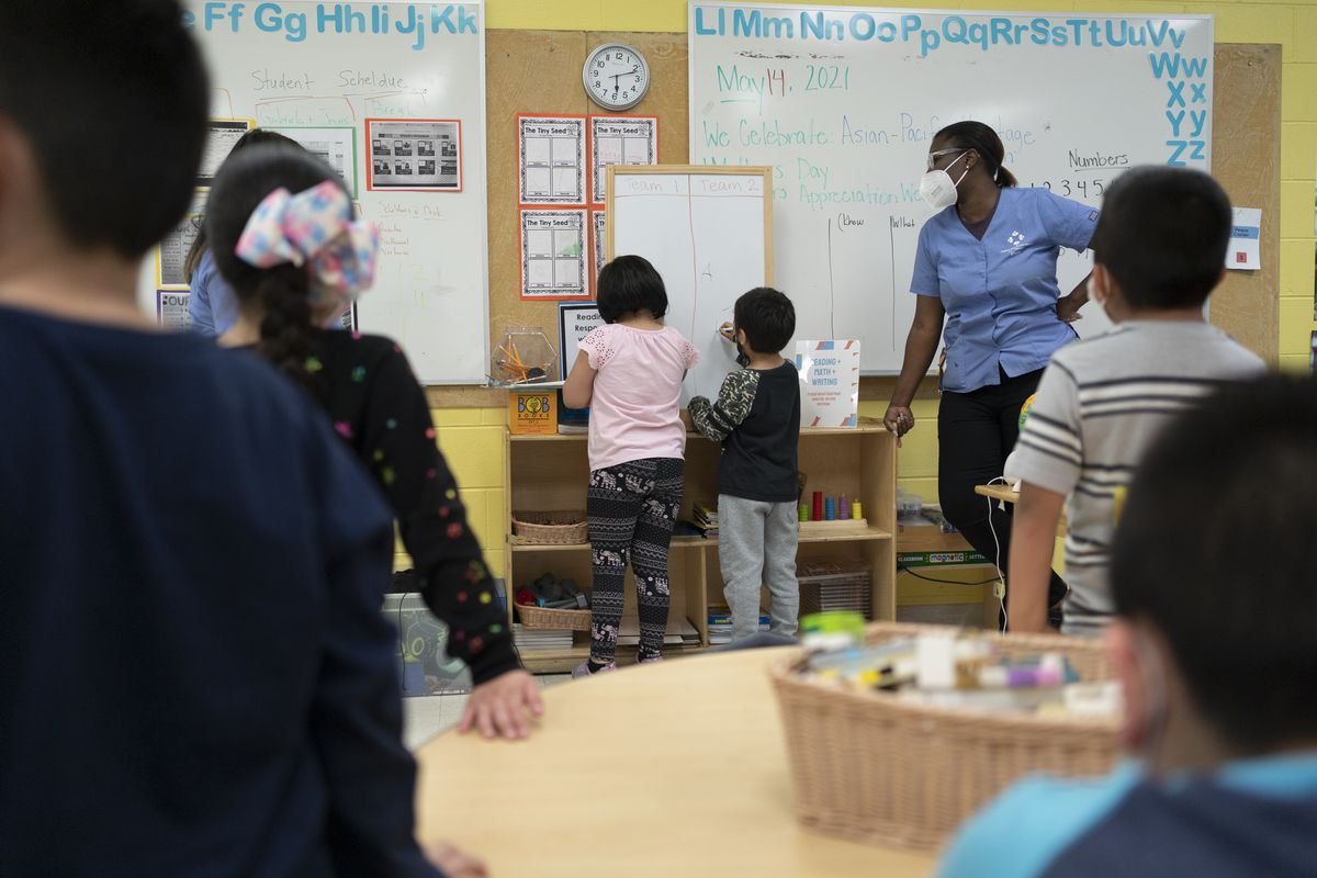 Young students are lined up in front of a white board before participating in a classroom activity.