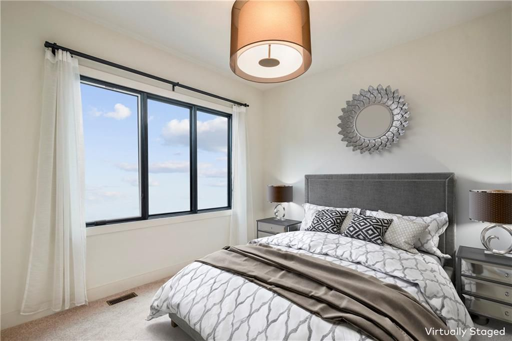 A white bedroom with white carpet and a virtual bed.