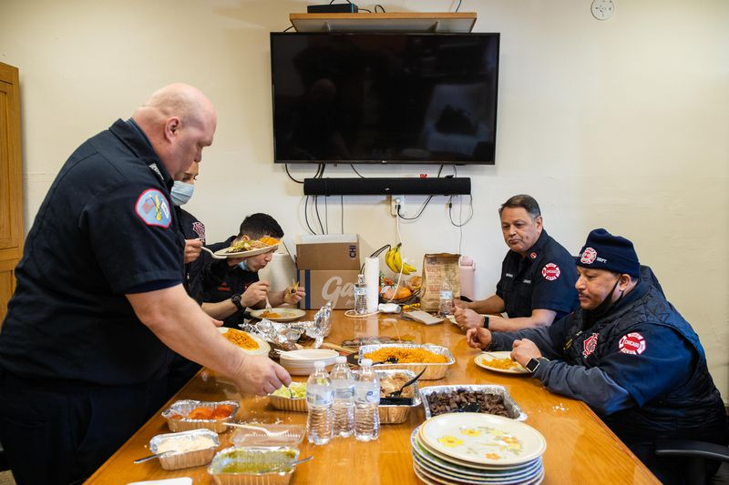 Chicago Fire Department firefighters at Engine 29 in Bridgeport eat food that was donated Thursday by White Sox pitcher Liam Hendriks and his wife Kristi.