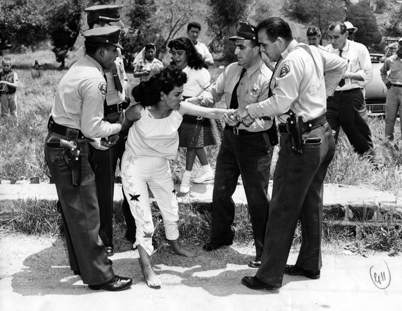 Archival black-and-white photo of four sheriff's deputies gripping the wrists of a barefoot woman as she resists.
