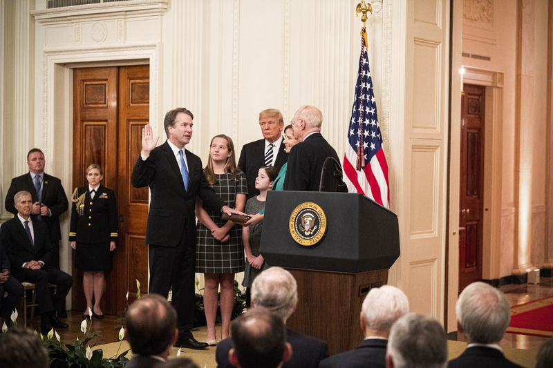 Supreme Court Justice Brett Kavanaugh holding up his right hand as his swearing-in ceremony.