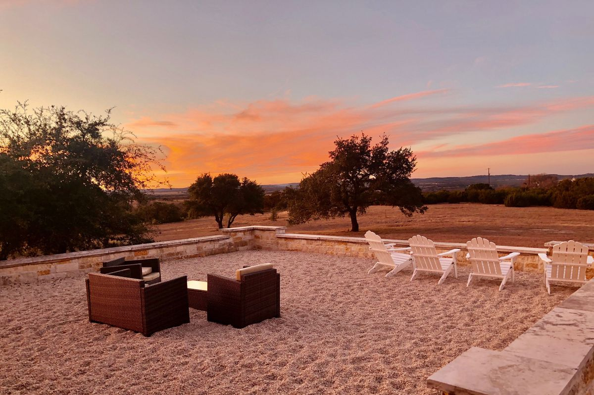 A graveled patio with a grouping of low wooden armchairs and white lawn chairs overlooking grass and trees during sunset.