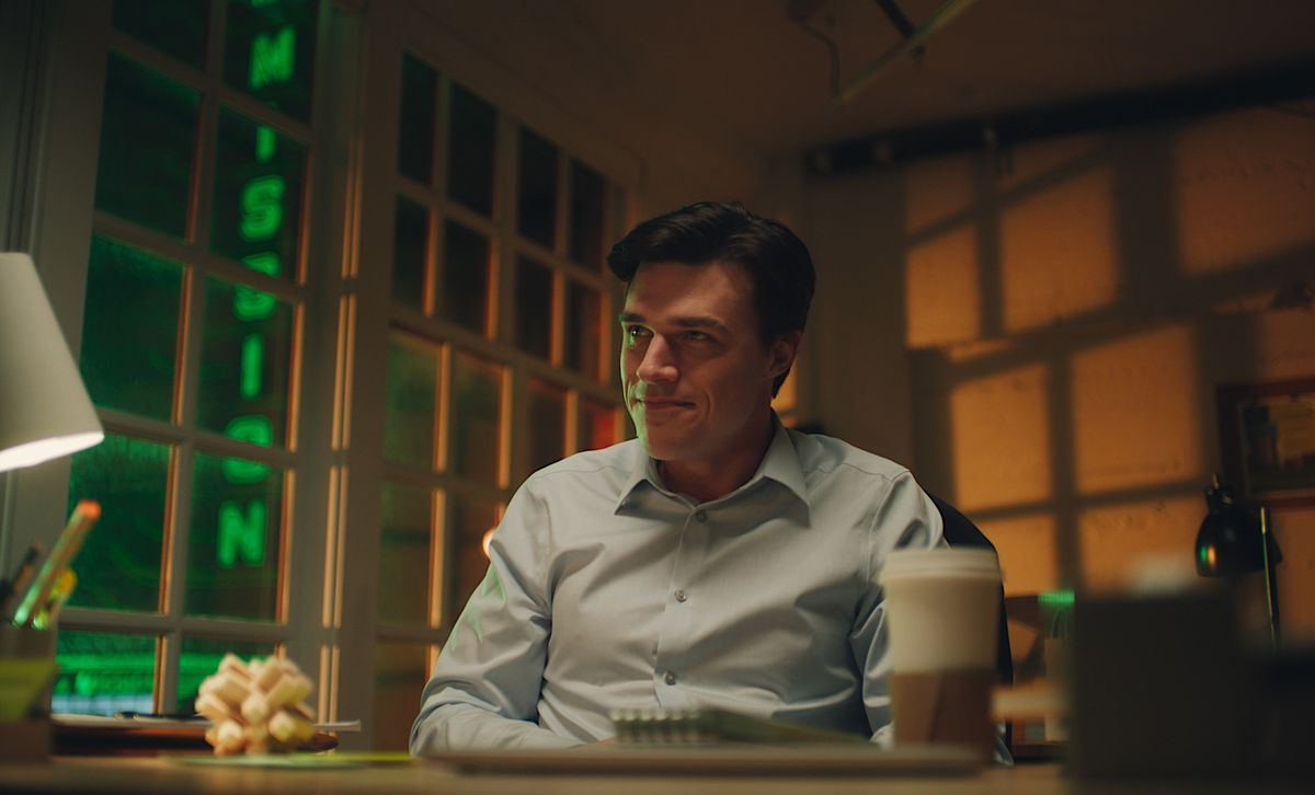 Finn Wittrock, who plays realtor Clayton Newsom, sits in an office across the street from the neon New Mission Theater signage.