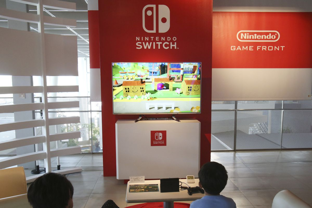 Visitors play a Nintendo Switch game at a showroom in Tokyo, Tuesday, July 30, 2019.