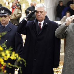 German Capt. Paul Roth, President Dieter F. Uchtdorf and Elder Robert C. Oaks salute as taps is played during Volkstrauertag ceremony.