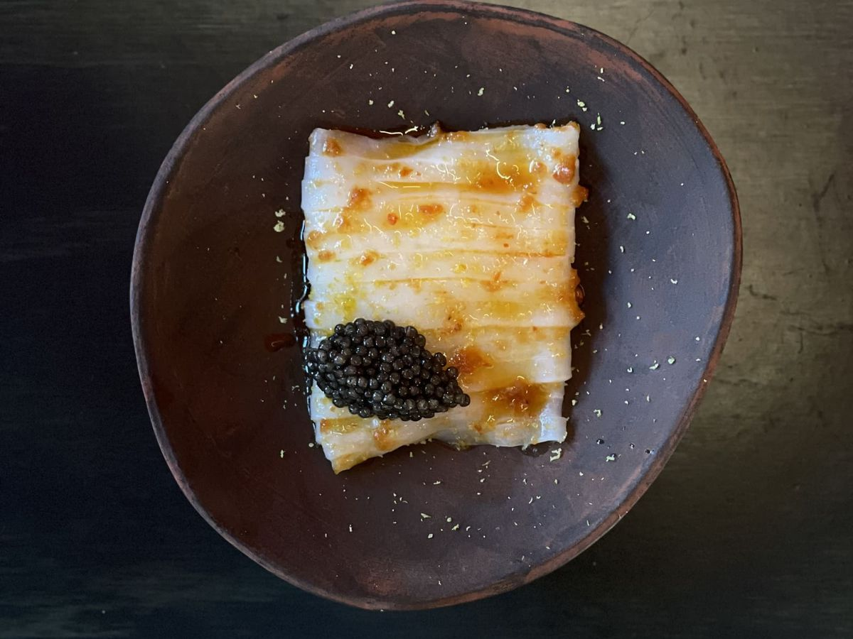 Slices of squid on an oblong ceramic plate topped with caviar