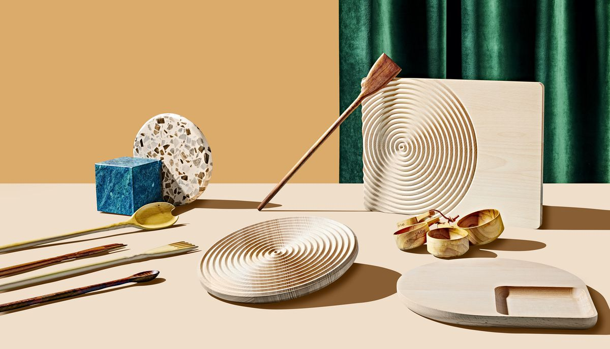 A grouping of products which are part of the 2019 Curbed Holiday Gift Guide. There are wooden cutting boards, measuring cups, wooden utensils, and other design objects arranged on a flat surface. In the background is green fabric and an orange backdrop.