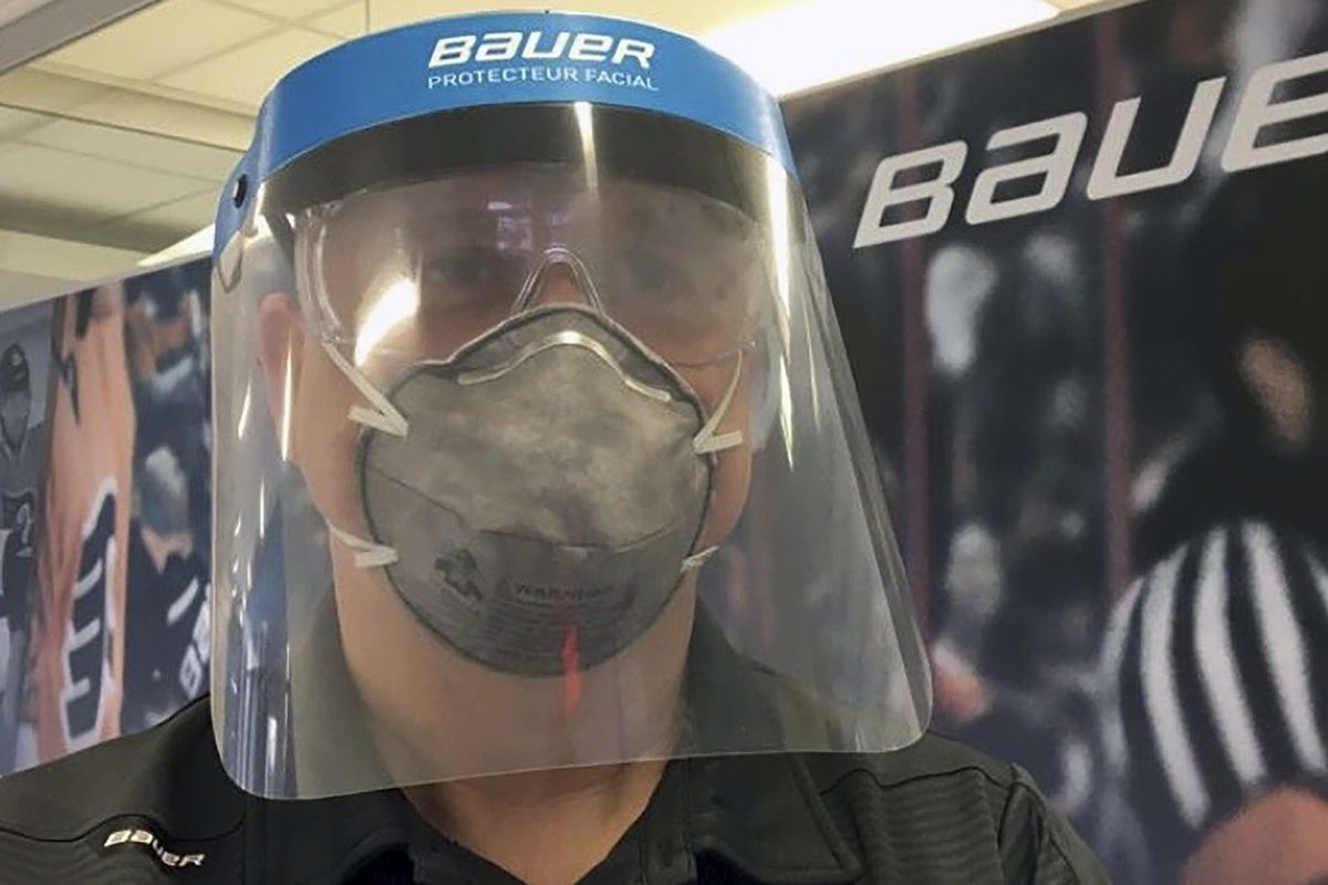 A Bauer employee models a medical face shield the hockey equipment manufacturer has begun creating to help those treating the coronavirus pandemic.