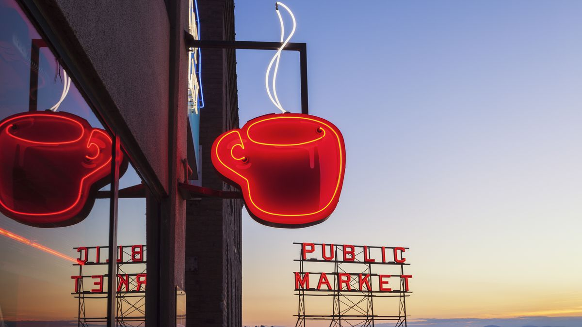 A glowing red coffee cup sign with the Pike Place Market marquee in the background