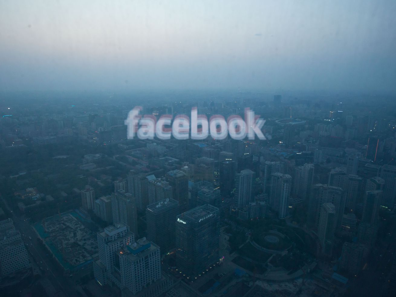 The Facebook logo reflected in a window looking out over a smoggy city.